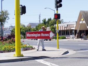 On Webster St., Man displaying sign showing the way to Bayport, Alameda, California, July 11, 2004